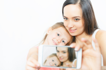 megapixel: Cute child and mother make selfie on new mobile phone with good camera. Twenty megapixel. Daughter and mum looking at the camera and smiling. Mothercare is most important in childs life