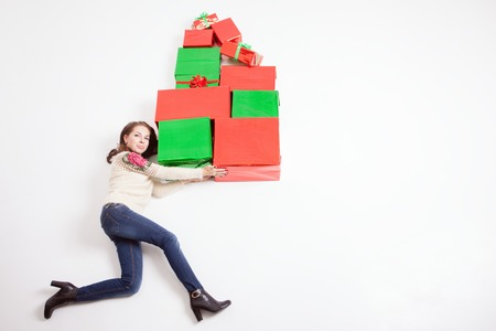Cristmas: Black Friday 2016 at United States! Funny mother holding many gift boxes for kids and running. Copy space at white background. Big gift box! Cristmas shopping. Xmas, New Year holiday! Merry Christmas! Stock Photo