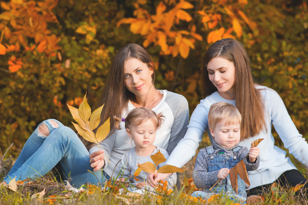 fall protection: Alternative lesbian family with mothers, daughter and boy outdoor. Fall season. Protection rights. Healthy concept. Mothercare is most important in baby life
