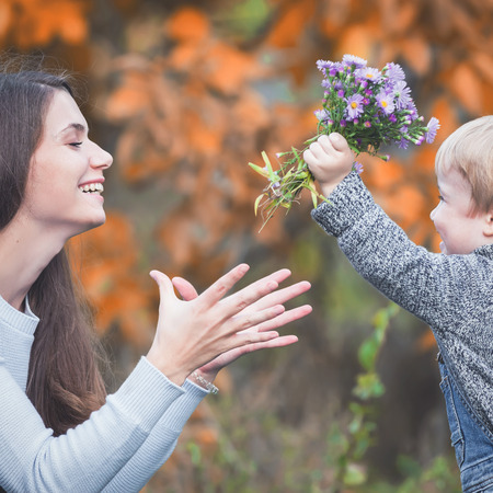 mothercare: Child gives to happy mother flowers. Fall colors background. Happy Family Values. Baby boy and mom. Mothers care most important in baby live. Autumn. Childrens Day, Mothers Day Stock Photo