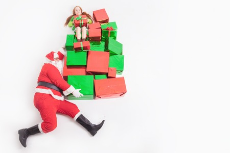 Black Friday 2016 at United States Funny Santa delivering many gift boxes for kids. Little girl sitting at top of big gift box, and holding present. Copy space at white background. Cristmas shopping Stock Photo