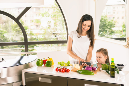 Cute little girl cooking with her mother in the bright modern kitchen. Healthy food, cooking healthy salad with vegetables ingredients. Mom and daughter looking the recipe on mobile phone