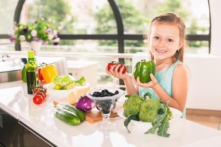 Cute little girl cooking. Child holding a bell pepper and cherry tomato. Healthy food, cooking salad with vegetables ingredients. Recipe. Nutrition