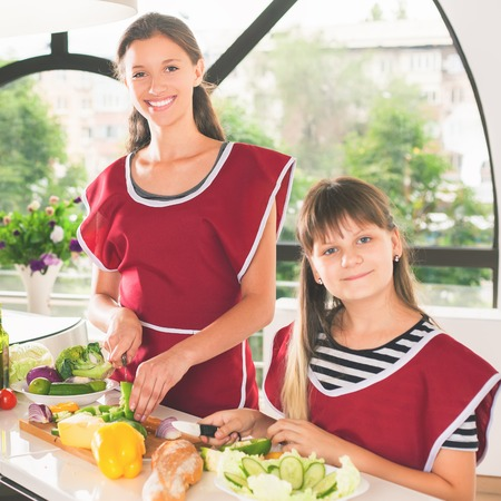 Happy family of young girls cooking. Vegetarian meal at kitchen. Funny sisters making salad. Healthy lifestyle. Recipe of vitamins nutrition. Girls looking at camera Stock Photo