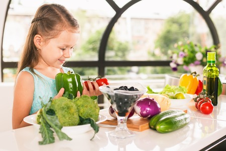 Cute little girl cooking. Chef, cook. Child holding a bell pepper and cherry tomato. Healthy food, cooking salad with vegetables ingredients. Recipe. Nutrition