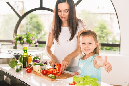 Cute little girl cooking with her mother and shows thumbs up. Healthy food, cooking healthy salad with vegetables ingredients. Mom and daughter cooking together. Recipe food for baby or child