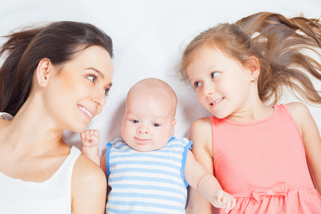 mothercare: Happy family, mother with daughter looking at baby. Newborn and child. Mothercare is most important in children life.