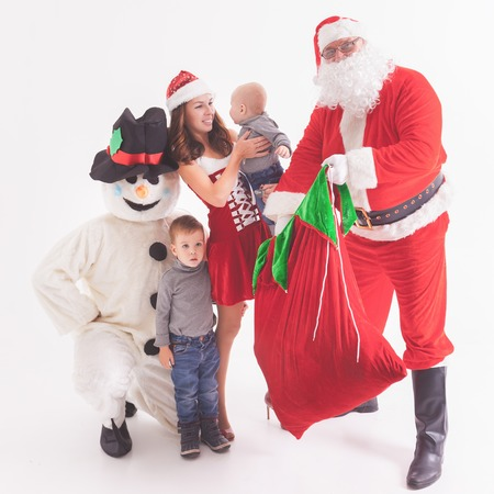Black Friday 2016 at US. Your father is Santa. Gives gift boxes for kids. Mother, children and snowman. Family celebrating Christmas. Xmas shopping