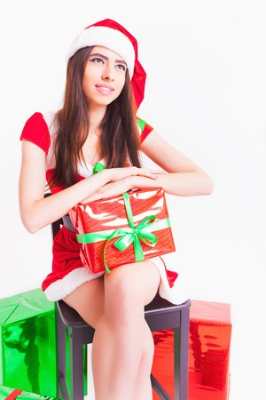 sexy latina: Beautiful latin woman holding a gift box at christmas day. Dressed in Santa hat and red dress. White background, copy space