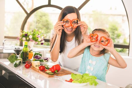Happy family keeps fresh pieces of bell pepper. Cute little girl cooking with her mother. Cooking vegetarian meal at kitchen. Making salad. Healthy lifestyle. Recipe of vitamins nutrition