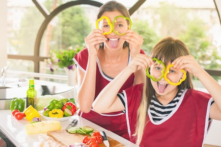 Happy family keeps fresh pieces of bell pepper. Cooking vegetarian meal at kitchen. Funny sisters making salad. Healthy lifestyle. Recipe of vitamins nutrition. Girls looking at camera
