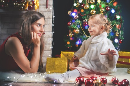 mothercare: Cute baby and mum decorating a Christmas tree. Red balls. New Year 2017. Fairy tale. Mothercare is most important in children life. Baby and daughter