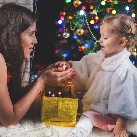 mothercare: Cute baby and mum decorating a Christmas tree. Red balls. New Year 2017. Fairy tale. Mothercare is most important in chiln life. Baby and daughter Stock Photo