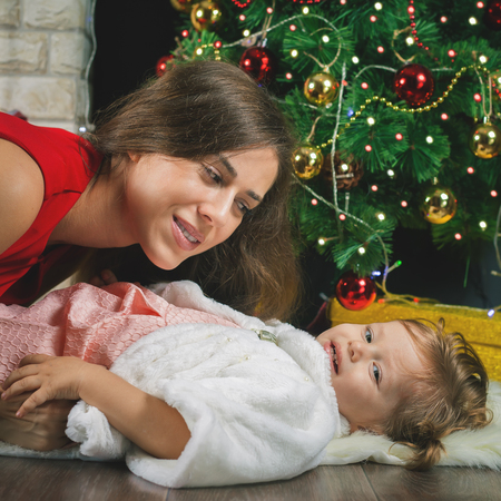mothercare: Funny baby and happy mum near Christmas tree. New Year 2017. Fairy tale. Mothercare is most important in children life. Baby and daughter