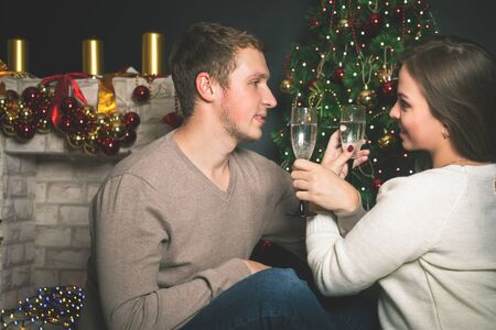 12 oclock: Couple young man and girl near the decorated Christmas tree celebrating New Year. Clink glasses. Christmas party, drinking champagne. Twelve oclock, midnight Stock Photo