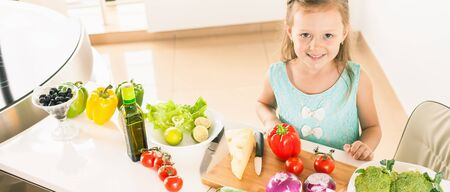 Cute little girl making salad. Child cooking. Healthy food