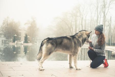 Afbeelding van een jong meisje met haar hond, malamute van alaska, outdoor