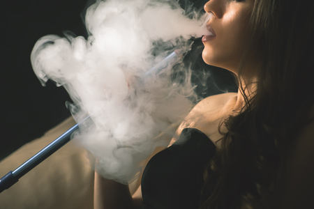 Young, beautiful girl smoke a hookah at club