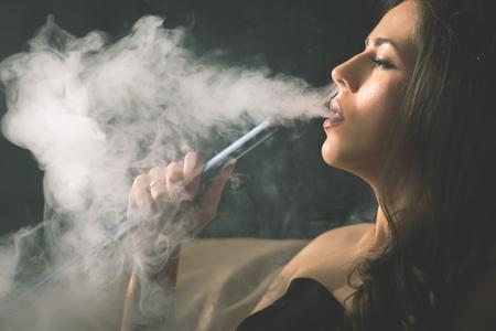 Junge, schöne Mädchen, das eine Wasserpfeife zu rauchen Club Standard-Bild - 73508671