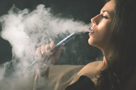 Young, beautiful girl smoke a hookah at club Zdjęcie Seryjne - 73508671