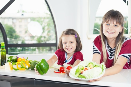 Cute little girl cooking with her sister, healthy food