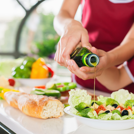 Women cooking fresh salad and pour olive oil. Healthy food