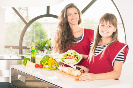 Happy family cooking salad. Vegetarian meal at kitchen Stock Photo