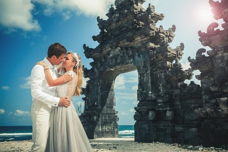 Portrait of happy couple near traditional gate. Traveling at Bali Stock Photo