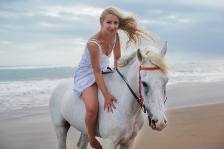 Beautiful young woman walking with horse at the beach, horseback