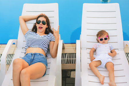 Endless summer. Cute baby and mother relaxing at sunbed Stock Photo