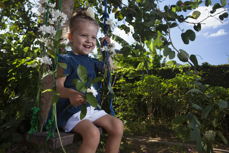 Happy little girl swing on Childrens Day or Mothers Day. Stock Photo
