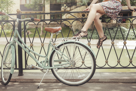 Young girl sitting on fence near vintage bike at park Stock Photo