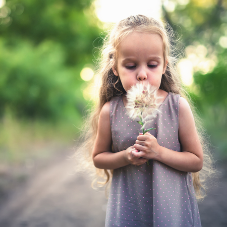 Your kid holds dandelion flower at autumntime
