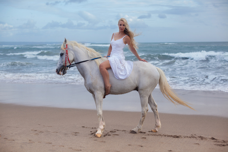 Sexy young woman walking with horse at the beach, horseback Archivio Fotografico