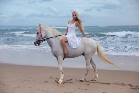 Giovane donna sexy che cammina con il cavallo in spiaggia, a cavallo