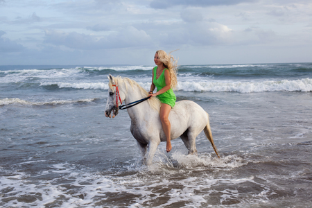 Sexy young woman walking with horse at the beach, horseback Stock Photo