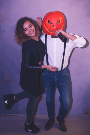 Unusual couple with pumpkin at the Halloween party