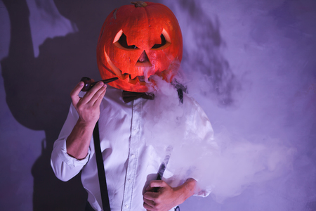 Handsome Man with carved pumpkin on his head for Halloween party smokes smoking pipe Stock fotó