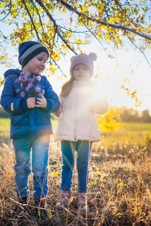Happy kids walking outdoor at park hold their hands. Stock Photo