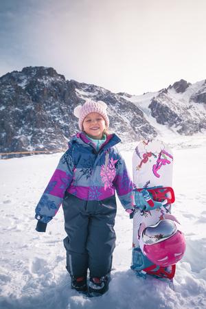Your happy kid has ski or snowboard lesson at alpine school 写真素材