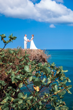 Newlyweds, bride and groom near the picturesque blue ocean