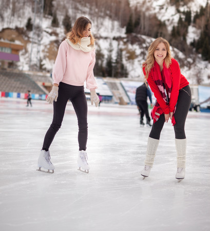 women ice skating outdoor at ice rink