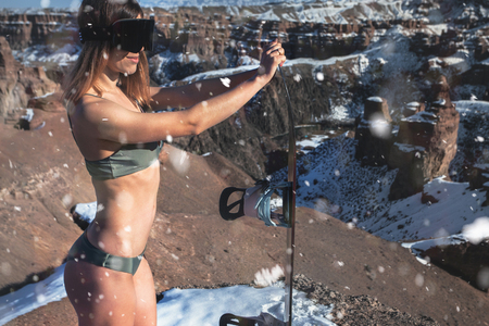 Naked sexy snowboarder girl with snowboard and ski glasses at unusual amazing the Charyn Canyon