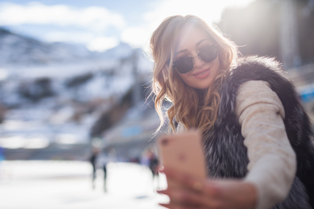 Beautiful girl making a selfie mobile phone at ice rink