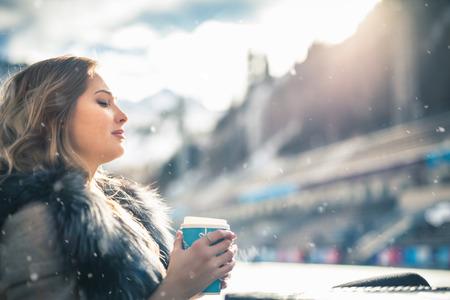 Beautiful girl resting and drinking coffee after ice skating Zdjęcie Seryjne