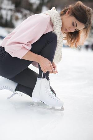 Woman tie shoelaces figure skates at ice rink close-up Zdjęcie Seryjne