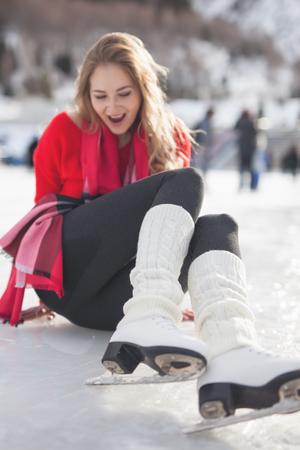 Happy girl sitting at ice. Woman ice skating outdoor Zdjęcie Seryjne