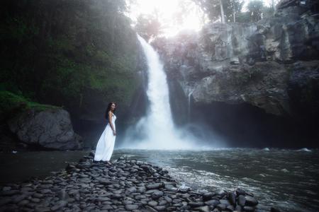 Happy woman near big waterfall traveling at Bali, Ubud. Summer
