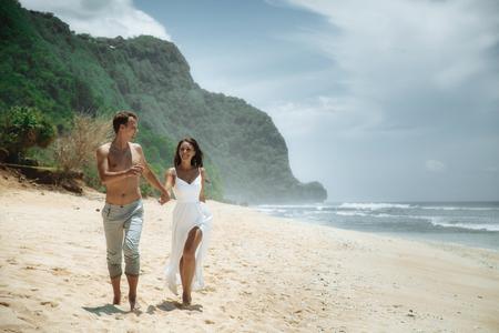 Happy couple walking at the beach, traveling at Bali. Zdjęcie Seryjne