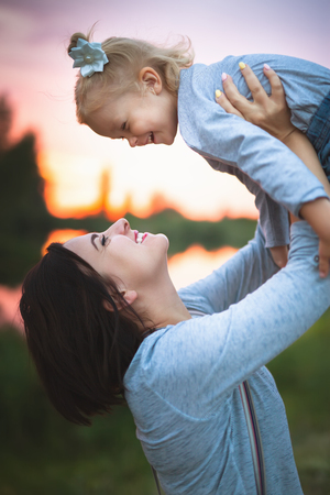 Beautiful young woman and her charming little daughter are hugging